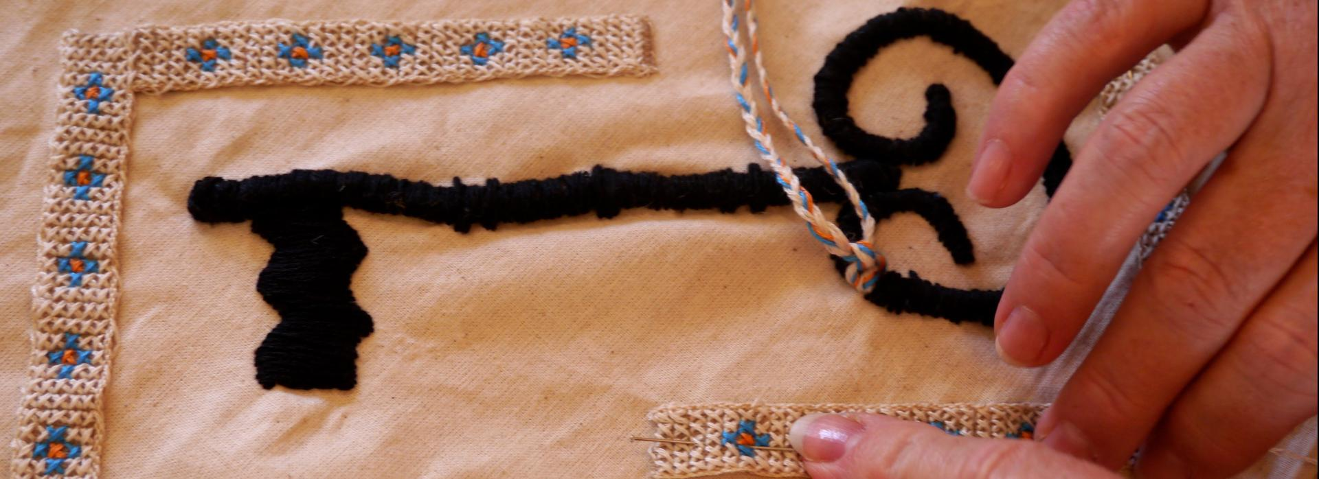 a close-up of two hands working on an embroidery of a key