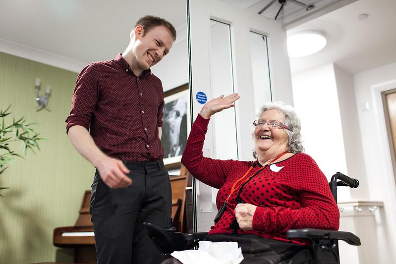 a young man and an older woman laughing together