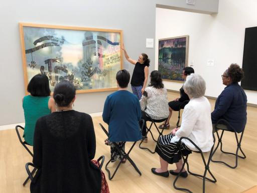 a woman discusses a picture at the Crocker Museum with a group of seated women